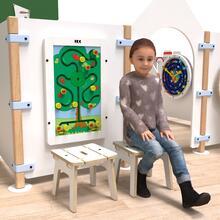 Op deze afbeelding ziet u een kind op de Buxus Stool white uit de kindermeubel collectie Buxus